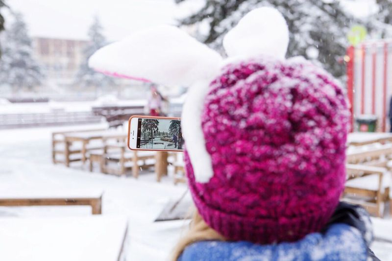 Rear View Of Woman Wearing Knit Hat Photographing Snow In City