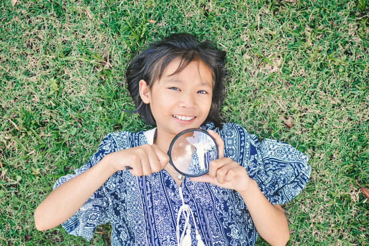 High angle portrait of girl holding magnifying glass while lying on grassy field