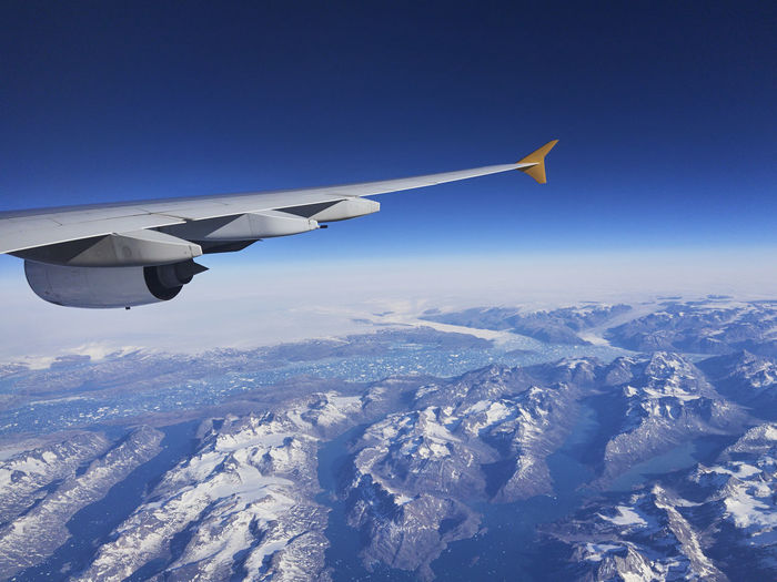 Airplane flying over snowcapped mountains against clear sky
