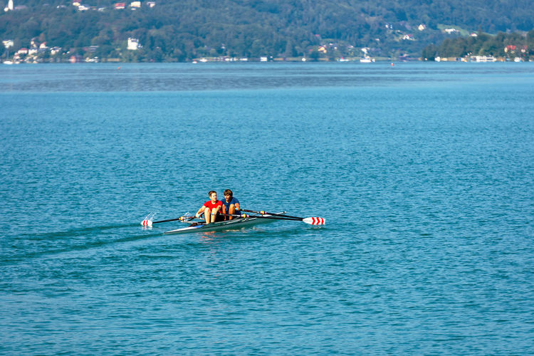 WORTHERSEE, AUSTRIA - AUGUST 08, 2018: View from the boat on the lake and young people engaged in the sport of rowing. Nature Day Outdoors Austria Carinthia Carinthian Lakes Tourist Tourists Lake Wörthersee Recreation  Leisure Landscape Water Sea Boats Motorboat Speedboats Summer People Holidays Fun Travel Beach Resort Lifestyle Sunny Rest Joy Waves Europe Alps Alpine Alpine Lake Nautical Vessel Transportation Waterfront Mode Of Transportation Real People Lifestyles Beauty In Nature Leisure Activity Men Scenics - Nature Group Of People Rowing