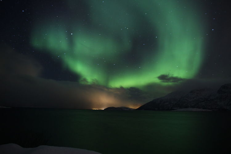 Scenic view of lake against sky at night with northern lights