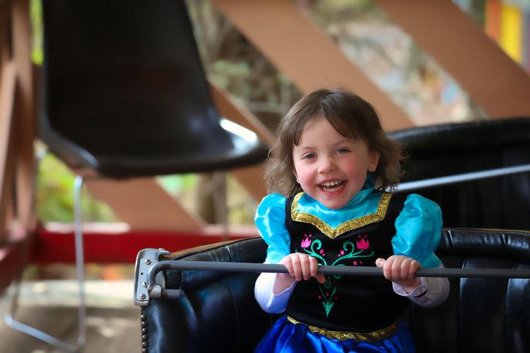 Portrait of smiling cute girl sitting in bumper car at amusement park