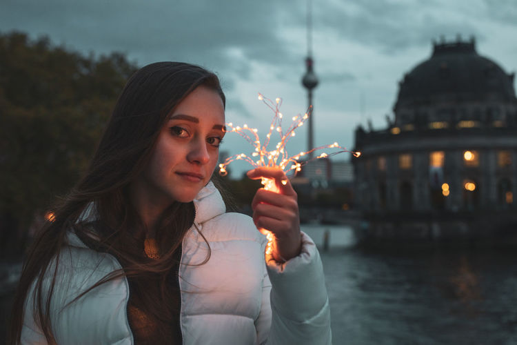 Portrait Of Young Woman Holding Illuminated Lights With Fernsehturm In Background