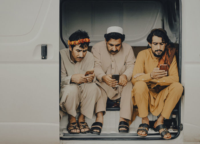 Men using smart phones while sitting in vehicle