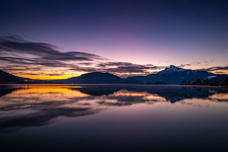 Scenic view of tranquil lake by mountains against romantic sky
