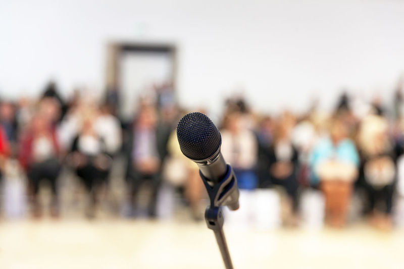 Close-up of microphone with people in background at auditorium