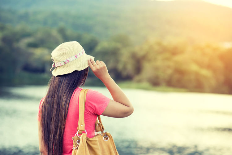 Traveler Asian woman still looking at the beautiful of landscape happily. vintage color effect Holiday Relaxing Travel Woman Day Lake Leisure Activity Lifestyles Nature One Person Outdoors People Rear View Scenics Sky Standing Sunlight Vacation Water Women Young Women