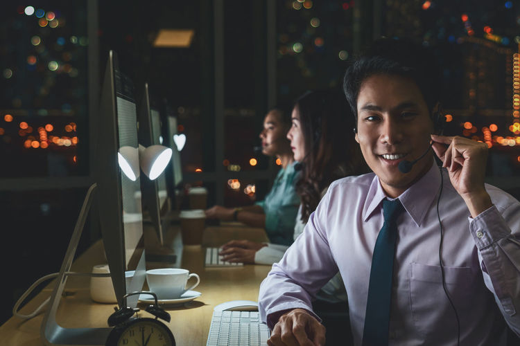 Portrait of businessman working at desk with coworkers in background