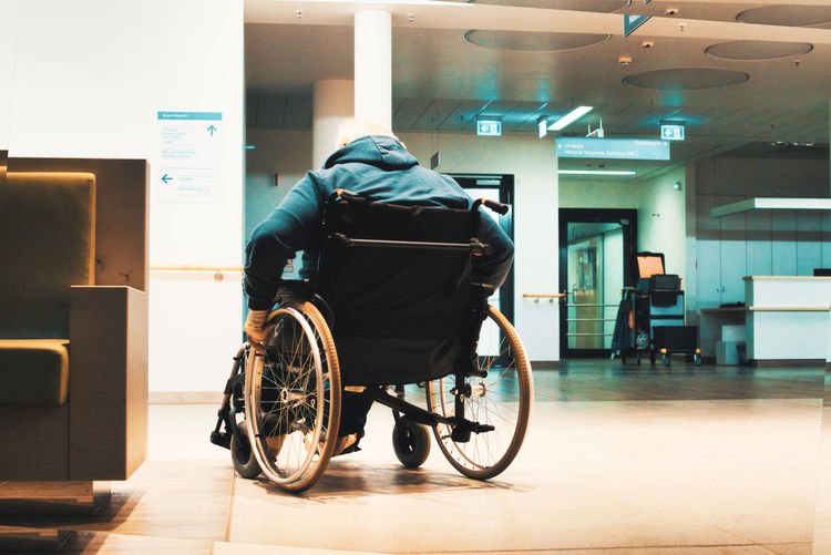 Rear view of man sitting in wheelchair against building in hospital
