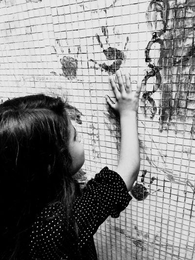 Side view of girl hand printing on wall