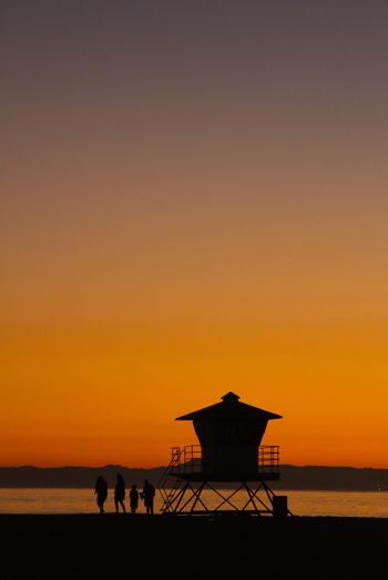 Silhouette Lifeguard Hut At Beach Against Clear Orange Sky During Sunset