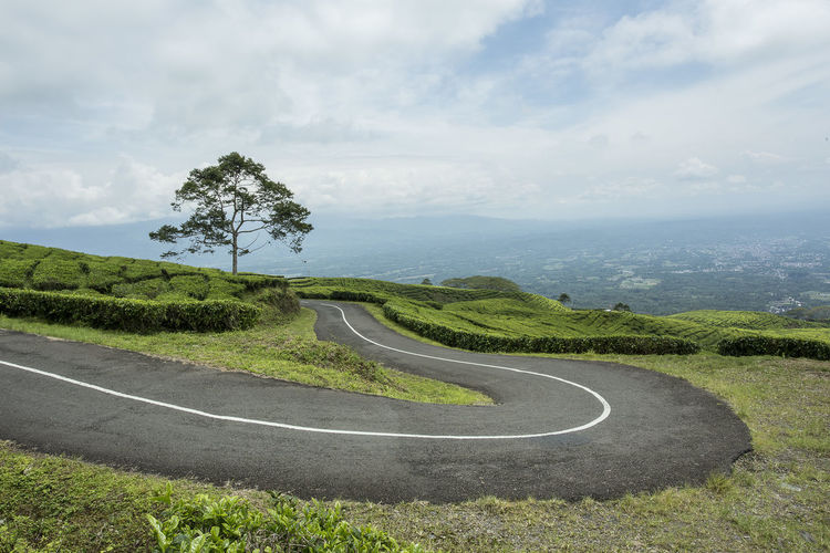 Scenic view of road by landscape against sky