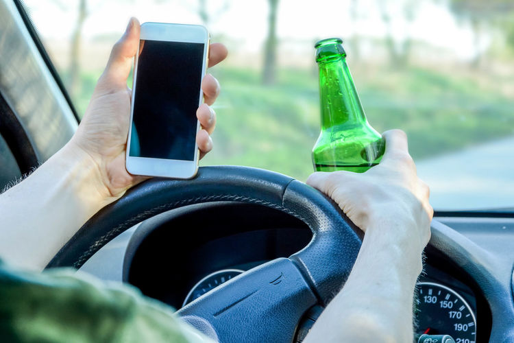 Close-up of man holding mobile phone and beer bottle while driving