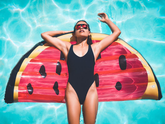 Beautiful Woman Beauty Bikini Day Floating On Water Inflatable Ring Leisure Activity Lifestyles One Person One Piece Swimsuit Outdoors Portrait Real People Red Relaxation Summer Sunglasses Swimming Swimming Pool Swimwear Three Quarter Length Vacations Water Young Adult Young Women