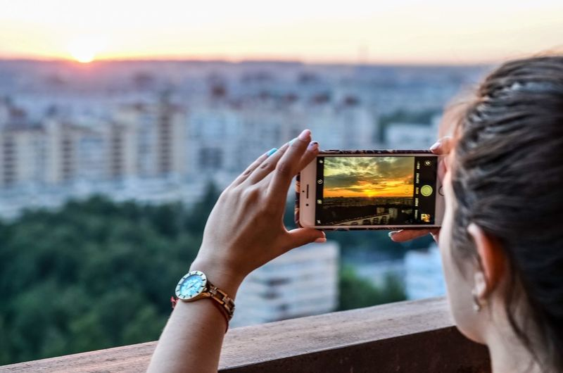 Midsection of woman photographing against sky during sunset