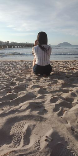 Rear View Of Young Woman Looking At Sea While Sitting On Beach Against Sky