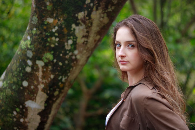 Beautiful Woman Close-up Day Focus On Foreground Leisure Activity Lifestyles Long Hair Looking At Camera Nature One Person Outdoors People Portrait Real People Side View Standing Tree Tree Trunk Young Adult Young Women