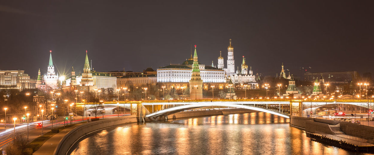 Night wide angle panoramic view of moscow downtown with kremlin, bridges and river reflections