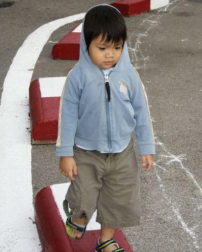 Boy wearing hooded shirt while walking on concrete block