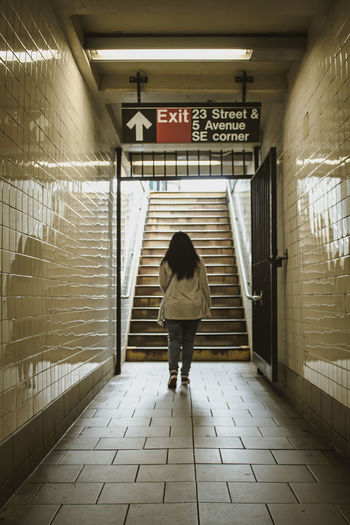 Rear view of woman walking up the stairs in subway in new york