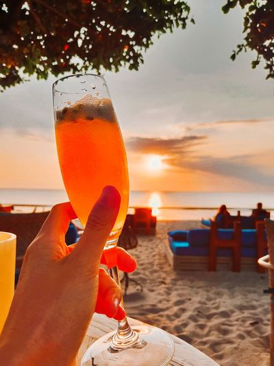 Close-up of hand holding drink at beach against sky during sunset