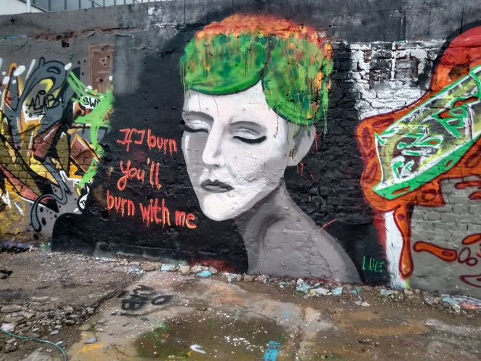 Close-up of statue against graffiti wall