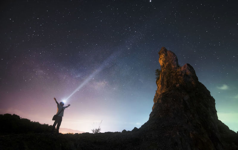 Low angle view of man with flashlight standing by rock formation against sky