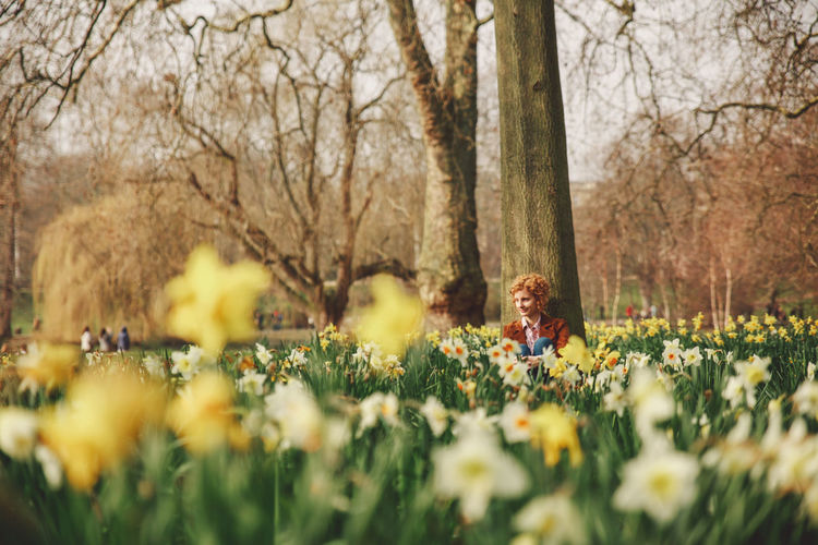 Young woman sitting amidst flowers at park