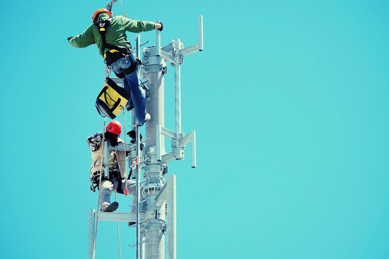 Low Angle View Of Technicians Repairing Electric Pole Against Clear Blue Sky