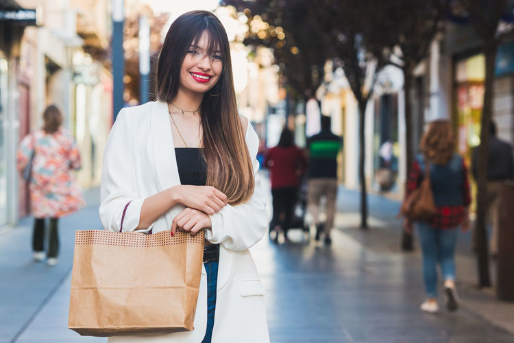 Portrait Of Beautiful Young Woman Holding Paper Bag While Standing In City