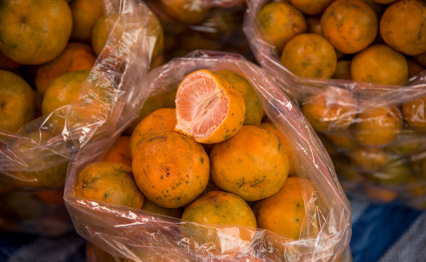 Directly above shot of oranges in plastic bags for sale at market
