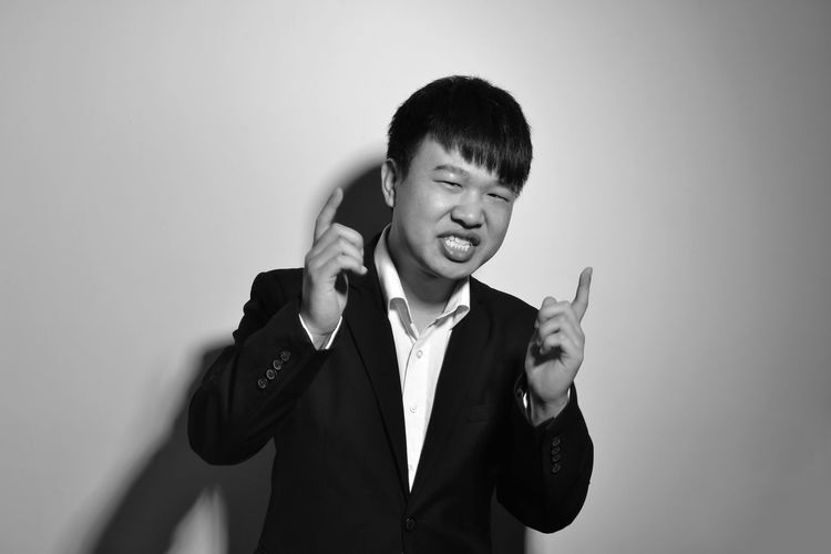 Portrait of young man pointing against gray background
