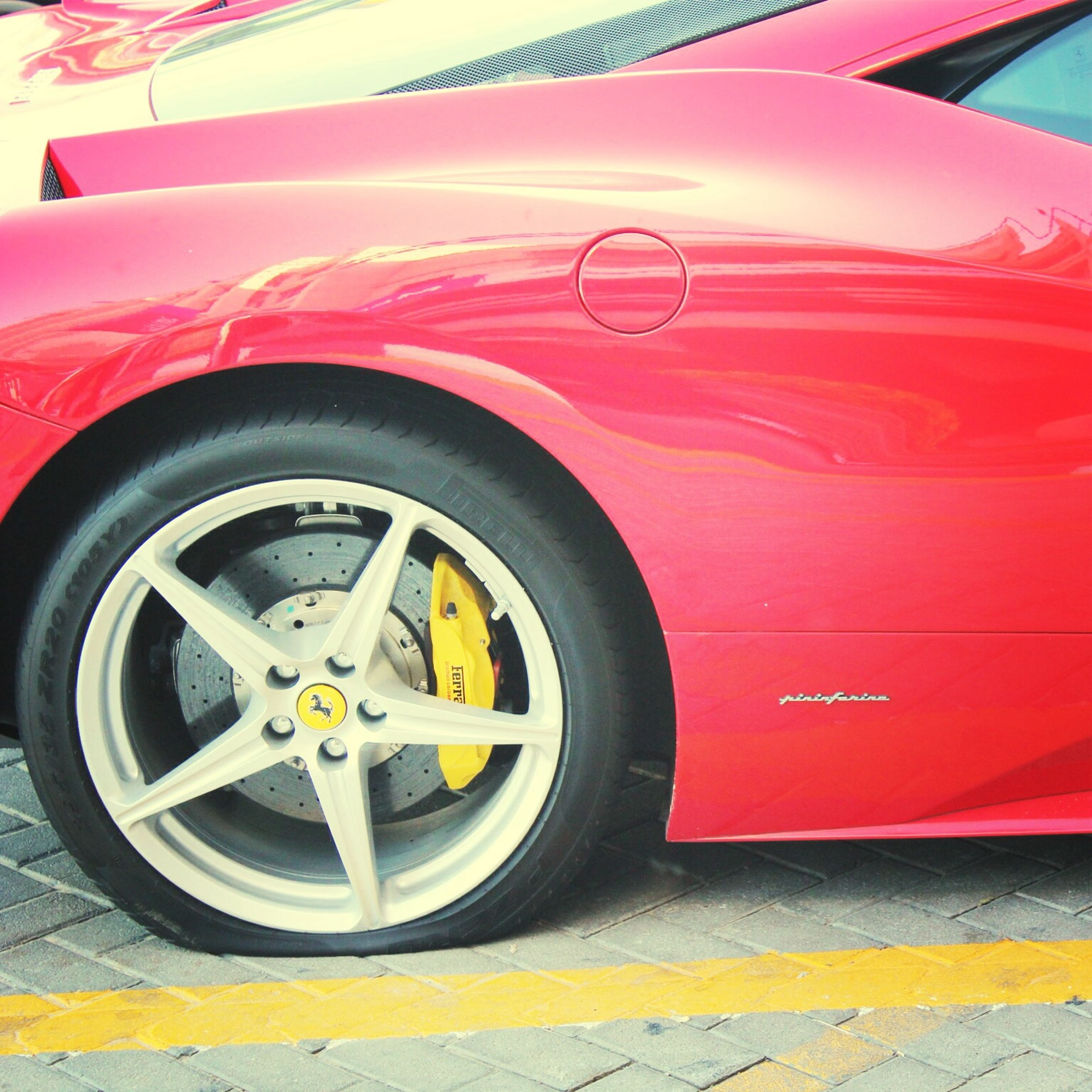 red, transportation, mode of transport, yellow, close-up, no people, day, wheel, built structure, land vehicle, outdoors, part of, architecture, building exterior, circle, old-fashioned, multi colored, low angle view, wall - building feature, stationary