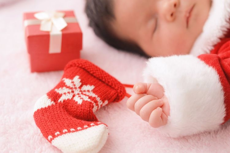 Close-up of baby girl holding christmas stocking while sleeping on bed