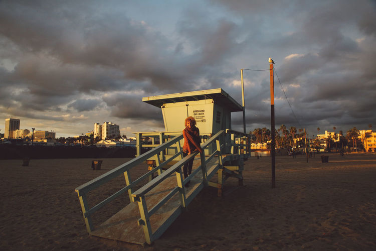 Portrait Of Young Woman Standing By Lifeguard Hut At Beach Against Cloudy Sky During Sunset