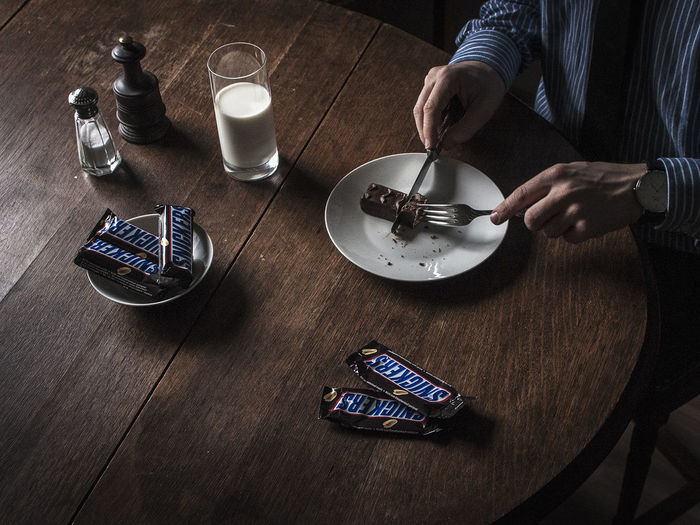 Table Setting Arts Culture And Entertainment Candy Food And Drink Formal Formal Style High Angle View Indoors  Milk No Face One Person Plate Seinfeld Snickers Table Wooden
