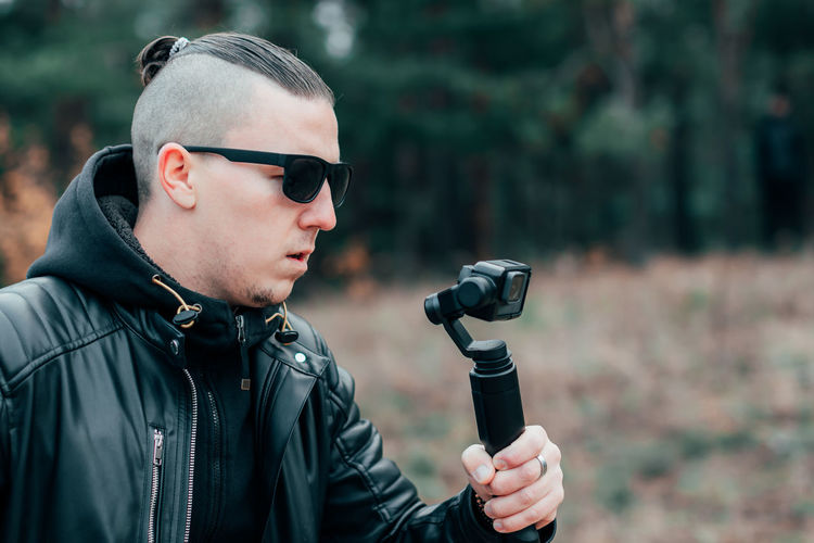 Young man filming with video camera
