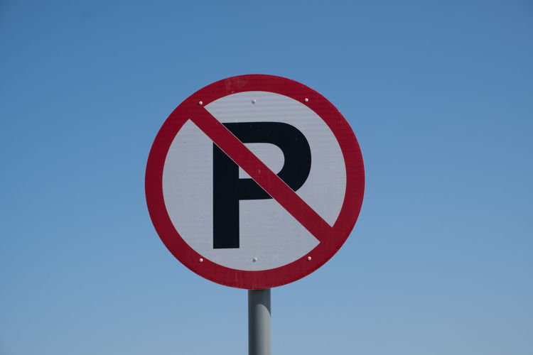 Low angle view of no parking sign against clear blue sky