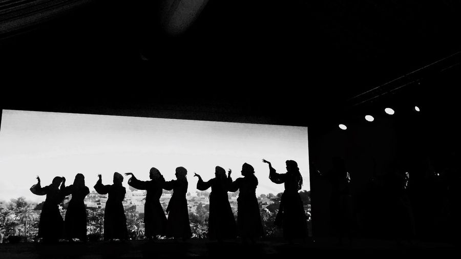 Silhouette people dancing against clear sky