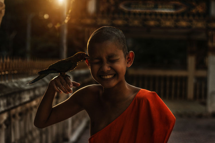 Close-up of smiling monk with parrot during sunset