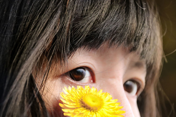 Close-up of woman with yellow flower looking away