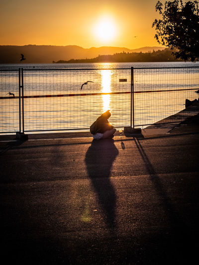 Silhouette man sitting on railing by lake against sky during sunset
