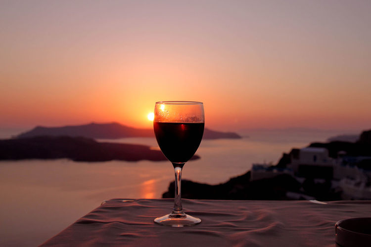 Close-up of wine glass on table during sunset