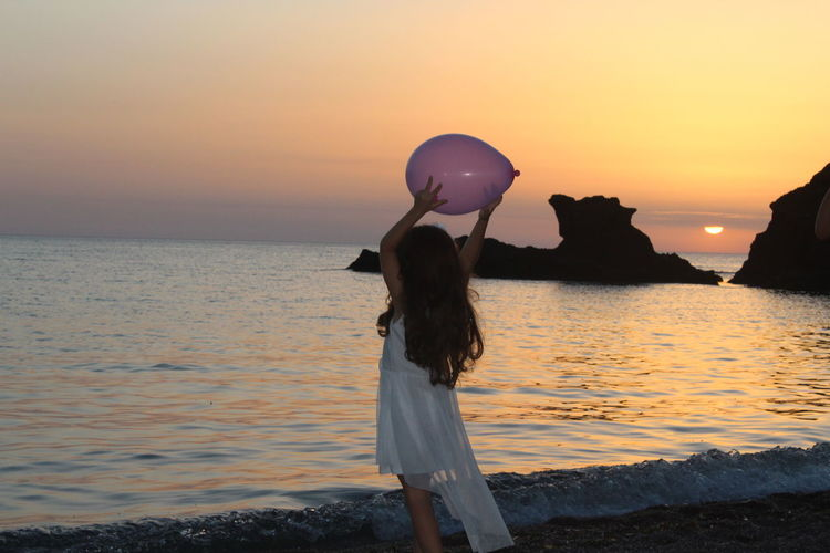 Girl holding balloon while standing by sea against sky during sunset