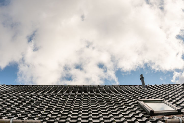 Low angle view of roof of building against cloudy sky