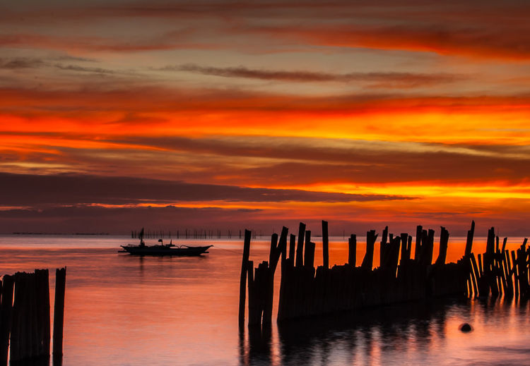 Water Sunset Sky Sea Beauty In Nature Scenics - Nature Cloud - Sky Orange Color Tranquility Nature No People Banca Boat Silhouette Bamboo Fences