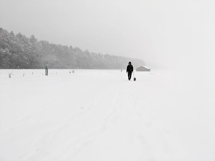 Unrecognisable person walking on snow covered land