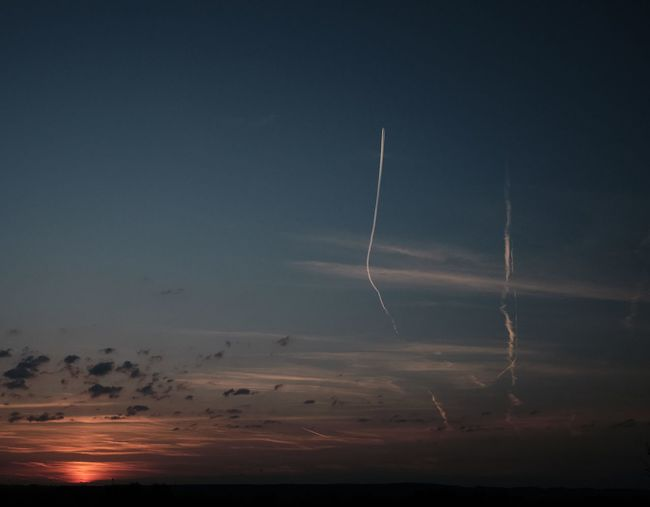 Low angle view of vapor trails in sky during sunset