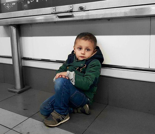 Portrait of cute boy sitting on floor