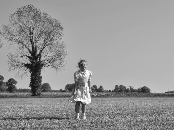 Full length of girl on field against clear sky